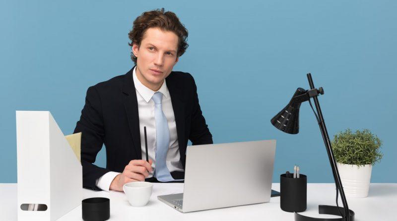 Homme assis avec un ordinateur portable sur son bureau